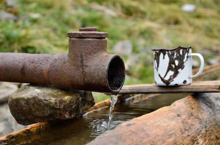 corroded: Clear water are flowing from the pipe in the wooden trough  A rusty mug is near