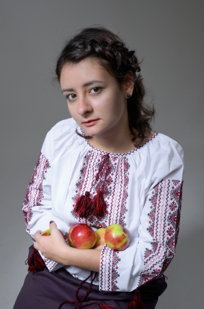 national costume: Cute young woman is holding apples and gazing. She is wearing a Ukrainian national costume (a white shirt embroidered and a skirt).