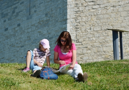 A woman and a girl are sitting on the green grass under the old brick wall  Tourists are examining a map  photo