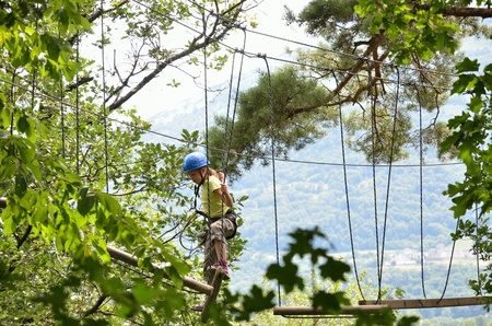 trapeze: A preteen girl is climbing on the trapeze bar at the obstacle course high up  He is photographed from below in the green forest  Stock Photo