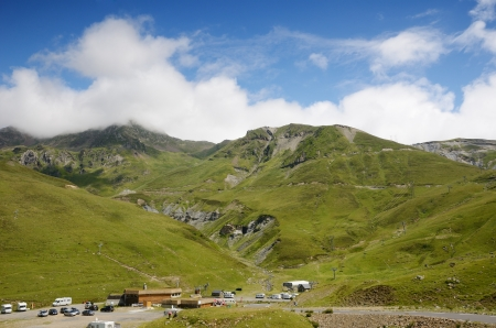 There are green slopes of mountains from the pass of Tourmalet in Pyrenees. Remote peaks are covered with white clouds. A serpentine road is prepared for the cycle race. photo