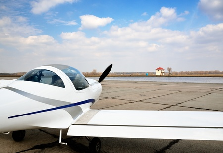 twoseater: A modern light plane is on the aerodrome against the sky.  Stock Photo