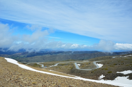 meandering: Serpentine road is meandering on the slope with snowfields in the Andalusian Sierra Nevada  Mountainside of Veleta is photographed in spring