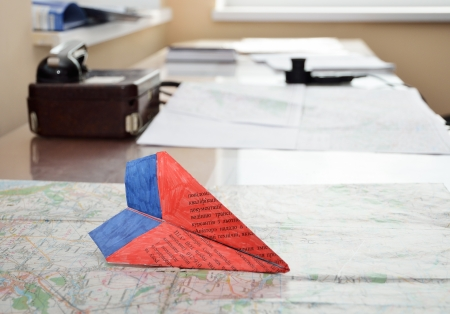 interphone: Paper model of an aircraft is on the flight chart  There is a speaking device on the table in the background