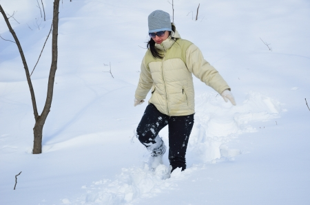 A woman is working her way through snowdrift in the winter park