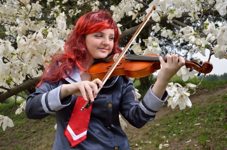 animation teenagers: A happy teenage girl is playing the violin in the flowering garden  She is wearing an anime costume and a wig
