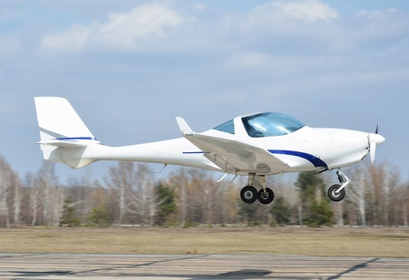 seater: A modern lightweight plane is landing or taking off on the aerodrome
