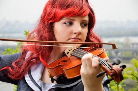 animation teenagers: A teenage girl is playing the violin outdoors  She is wearing an anime costume and a wig