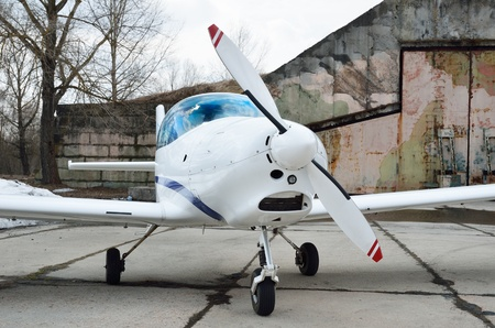 aerodrome: A modern light plane is near the hangar on the aerodrome