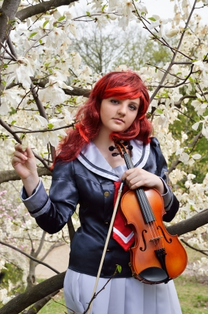 animation teenagers: A youth cosplayer with a violin in the flowering garden of magnolias  She is wearing an anime costume and a wig