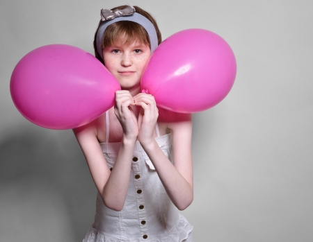 clasping: A teenage girl is clasping the pink balloons to her face  She is standing and looking at the camera  Stock Photo