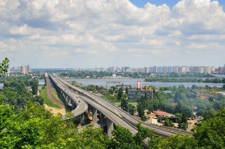 Wide river is dividing the city into right and left riverside  Both banks are overgrown with green trees and bushes  A modern bridge recedes into the left-bank residential district and the cloudy sky  photo