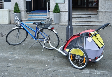 coherent: A city bike with a baby carriage are parked in the sidewalk of the German town