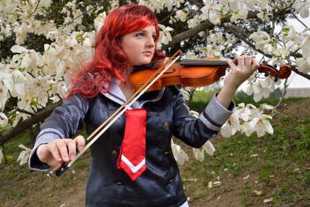 animation teenagers: A teenage girl is playing the violin in the flowering garden  She is wearing an anime costume and a wig