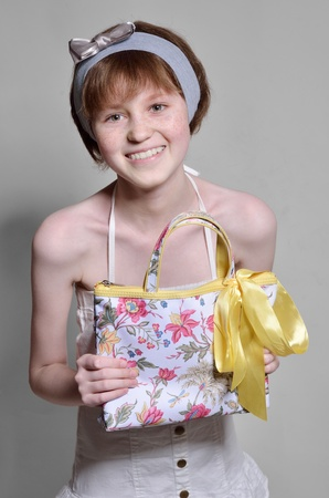 sincere girl: A teenage girl is smiling and looking at the camera  She is wearing a cotton sundress and a headband  She holds a bag with a bow