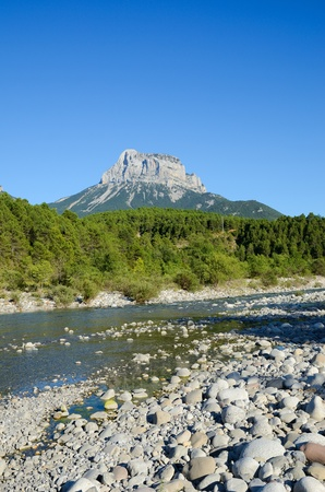 conspicuous: The Cinca river flows through the Spanish Pyrenees  In the background there is the Pena Montanesa  conspicuous rocky mountainous outcrop