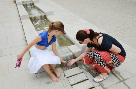 A woman and a girl are playing the water of the fountain in the ancient Basque town La Bastida-Clairence