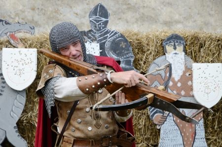 arbalest: A man is showing a crossbow  The arblaster is training at the festival of historical reenactment  He is wearing authentic clothing of the the Middle Ages