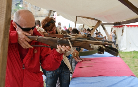arbalest: Spectators are shooting vintage crossbows at the festival of historical reenactment in the medieval castle Montaner