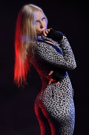 catsuit: Blonde woman is standing and looking intently in the dark  She is wearing a spotty sheath catsuit