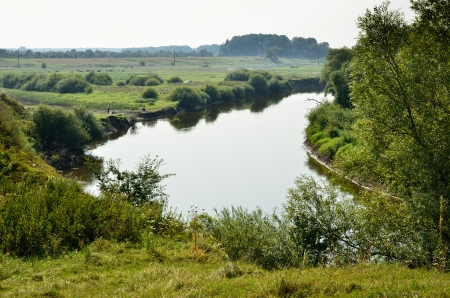 meandering: Summer green banks reflect in the water of the meandering river Western Bug  Stock Photo