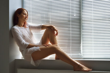 jalousie: A young pretty woman is sitting on the windowsill at home  A window is closed with jalousie  She is wearing a house dress  Stock Photo
