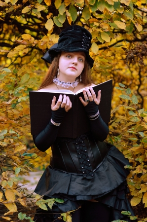 animation teenagers: A teenage girl with a big book in the autumn garden. She is wearing an anime costume of the undertaker.