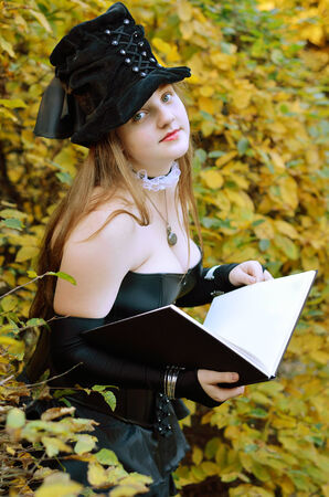 undertaker: A teenage girl with a big book in the autumn garden  She is wearing an anime costume of the undertaker