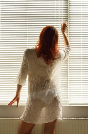 jalousie: A young woman is adjusting the jalousie on the window at home  She is standing in shaded light against the closed venetian blind