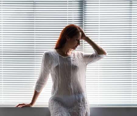 jalousie: A young woman is standing in shaded light against the closed venetian blind  She is wearing a transparent shirt