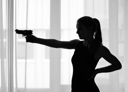 A slim young woman is aiming a pistol against the window  photo
