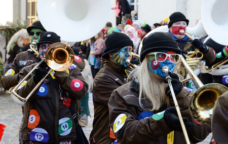 fasching: Orchestra of drawn mummers are playing and marching in the street of German city Konstanz at the traditional funfair Fasching