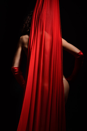 A nude woman is standing or dancing behind the red fabric  She is wearing only red gloves  Stock Photo