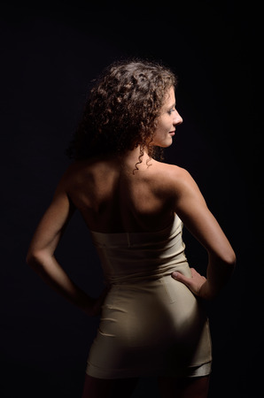 Young curly woman is posing backwards  She is wearing a strapless sheath short dress  Her sexy body is photographed in the dark with few highlights   photo