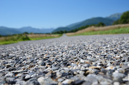 diminishing perspective: The road surface is photographed close-up with diminishing perspective  Tarmacadam a paving material that consists of crushed stone rolled and bound with a mixture of tar and bitumen  Stock Photo
