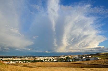 towering: Huge cumulus cloud is towering in the blue sky above the spring Spanish plain