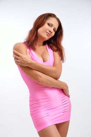 Young woman is posing in the rosy sheath short dress