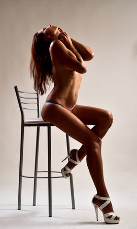 nude woman sitting: A nude woman is sitting on the high chair  She is petting herself  She is wearing a tiny panties and high heels