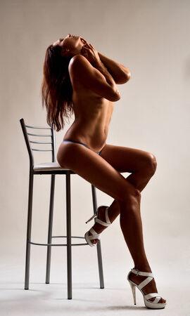 mujer desnuda sentada: Una mujer desnuda est� sentada en la silla alta Ella est� acariciando a s� misma Ella lleva una diminuta ropa interior y tacones altos Foto de archivo
