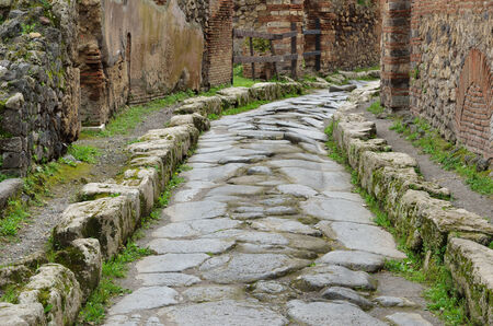 Narrow paved street is recovered in the middle of Roman ruins  Pompeii has been a popular tourist destination for over 250 years