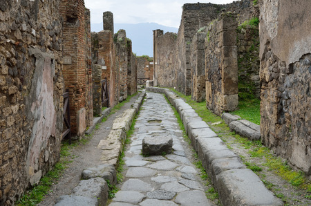 regenerated: Ancient paved street is recovered in the middle of damaged houses  Pompeii has been a popular tourist destination for over 250 years  Stock Photo