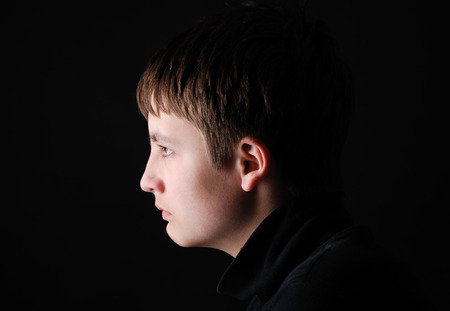 Upset teenage boy is photographed in profile on the black photo