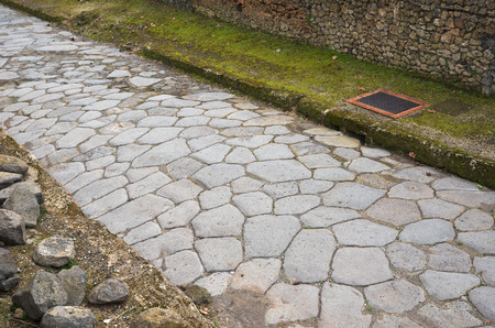Narrow paved road is in the middle of the ancient Roman ruins  Pompeii has been a popular tourist destination for over 250 years