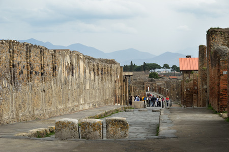 rehabilitated: Ancient paved street is recovered in the middle of Roman ruins against the mountains  Pompeii has been a popular tourist destination for over 250 years