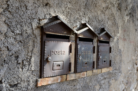 Three identical metal postboxes are in the stone wall  Stock Photo