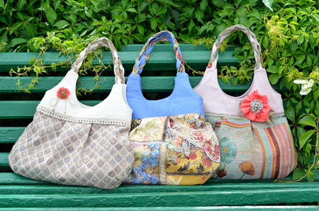 Three female handbags are on the bench  They are hand-crafted and made of the tapestry