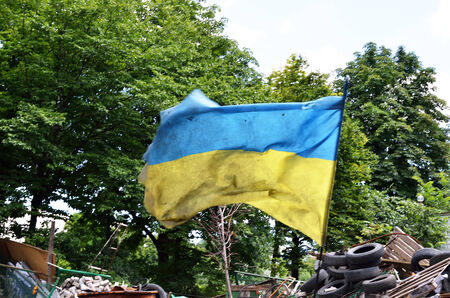 sooty: A yellow-blue banner is fluttering on the wind under the barricade in the Ukrainian capital  The torn sooty shot national flag is tried and tested in battle  Stock Photo