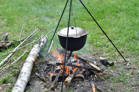 soup kettle: Blackened kettle with boiling soup is on the bonfire burning  It is hung on a metal tripod  Stock Photo