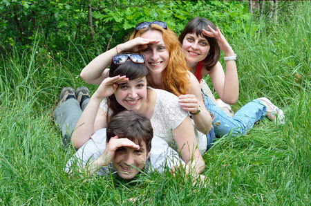 heap up: Happy young people heap up in the green grass  They are resting in the summer meadow