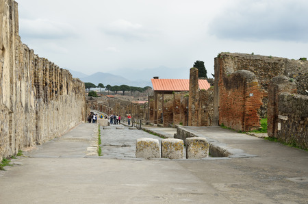 Ancient paved street is recovered in the middle of Roman ruins against the mountains  Pompeii has been a popular tourist destination for over 250 years
